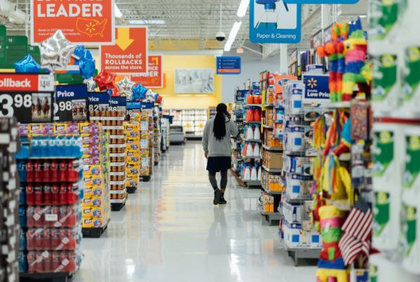A woman walks in a supermarket aisle.